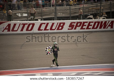 FONTANA, CA - MAR 23: Kyle Busch picked up the checkered flag after winning the Nascar Sprint Cup Auto Club 400 race at Auto Club Speedway in Fontana, CA on March 23, 2014 - stock photo