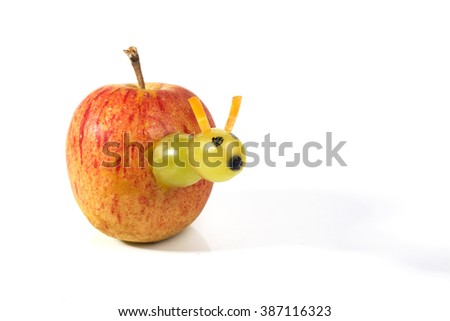 Food art creative concepts. A little worm made of green grapes and carrots is coming out of an apple on white background. - stock photo