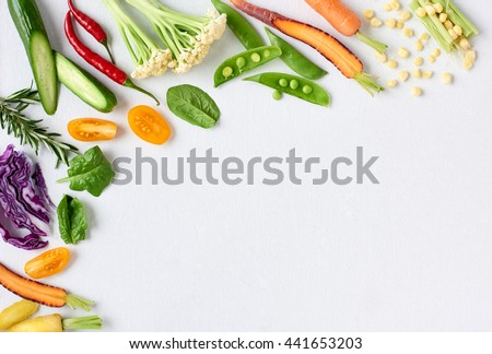 Food background border frame of colorful fresh produce raw vegetables, corn carrot chilli cucumber purple cabbage spinach rosemary herb, plenty of copy-space - stock photo