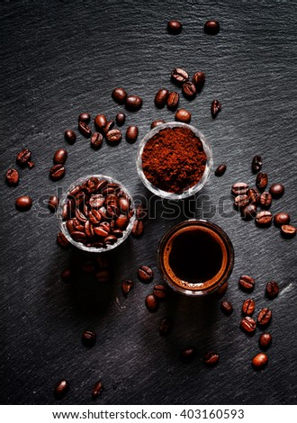 Food background: coffee beans, ground coffee, fresh espresso, dark background, top view - stock photo