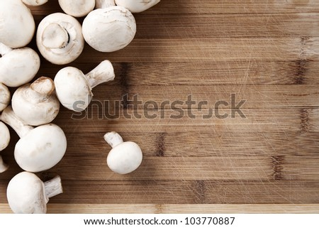 Food background of fresh champignons at the old cutting board with copy space - stock photo