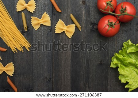 food background on rustic wood with pasta and tomatoes - stock photo