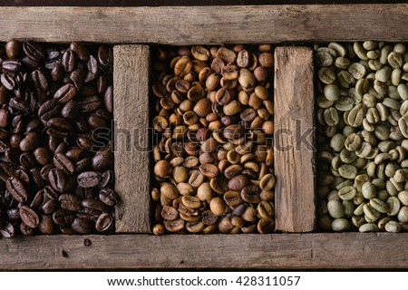 Food background with green and brown decaf unroasted and black roasted coffee beans in old wooden box. Top view. Close up - stock photo