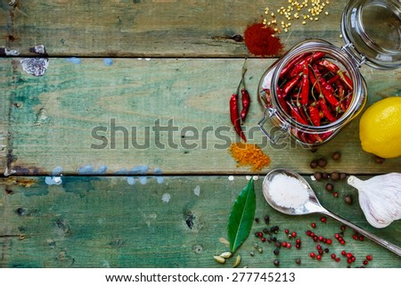 Food Background with Hot Peppers in glass jar, herbs and spices. Cooking or spicy food concept. Space for text. Top view. - stock photo