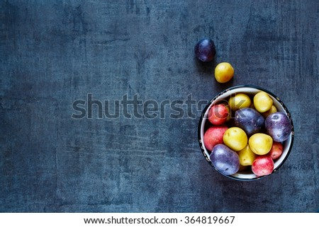 Food background with mixed varieties of fresh potatoes in vintage bowl over dark grunge table, top view. - stock photo