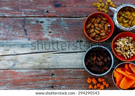 Food background with nuts and dried fruits over rustic wood. Healthy concept. Space for text. - stock photo