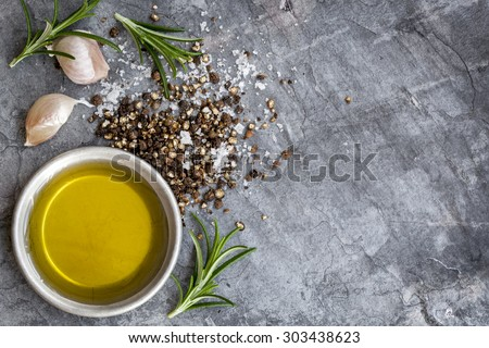 Food background with olive oil, peppercorns, sea salt, rosemary, and garlic cloves, over dark slate background.  Overhead view. - stock photo