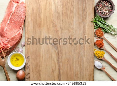 Food background with raw meat steaks and seasoning. Concept of ingredients for cooking steak, top view of raw meat, chopping board, virgin Olive Oil,  garlic, pepper, rosemary, salt, ground paprika - stock photo