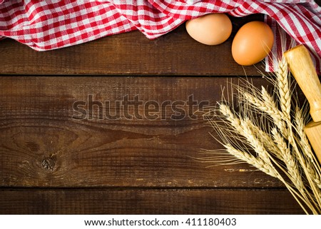Food background / Wooden background with plaid kitchen towel, fresh chicken eggs and golden wheat ears. Copy space for text - stock photo