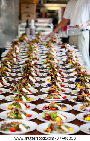food being plated at a wedding. this image has a very shallow depth of field - stock photo