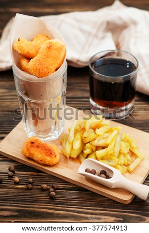 food, chicken nuggets and cola and fried potatoes on a wooden background - stock photo