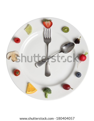 food clock made of fruits and vegetables on white plate  - stock photo