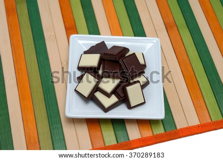 Food collection - A square plate with white and dark chocolate on a napkin of multi-colored wooden sticks. - stock photo