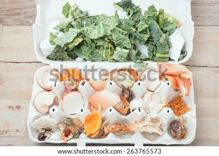 Food composting image: egg container filled with old food scraps, on rustic wooden background, top view - stock photo