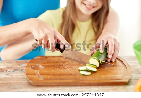 food, family, cooking and people concept - close up of happy girl and mother making dinner and chopping cucumber on cutting board with knife in kitchen - stock photo
