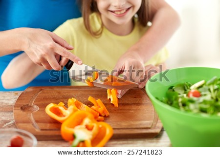 food, family, cooking and people concept - close up of happy girl and mother making salad for dinner and chopping paprika on cutting board with knife in kitchen - stock photo
