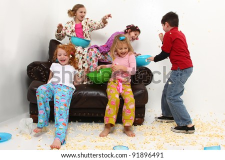 Food fight with brother at girl's pajama party sleep over with popcorn mess. - stock photo