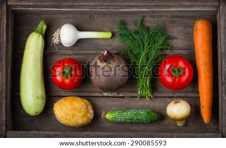 Food for raw foodists. Set of different fresh raw vegetables in an old wooden box: garlic, zucchini, tomato, carrot, cucumber, potatoes, beets, onions, dill. Harvest. Ingredients for vegetable dishes - stock photo