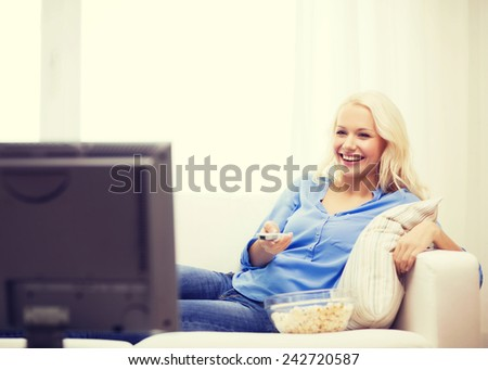 food, happiness and people concept - smiling young girl with popcorn watching movie at home - stock photo