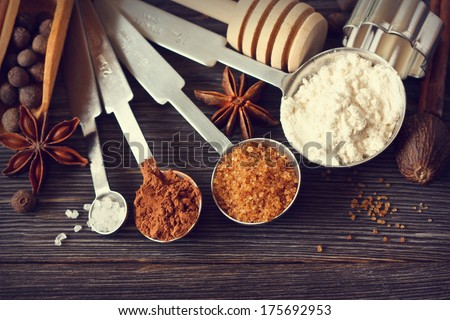 Food ingredients and kitchen utensils for cooking on a wooden board. Measuring spoons with cocoa, flour and brown sugar and spices. Toned photo.  - stock photo