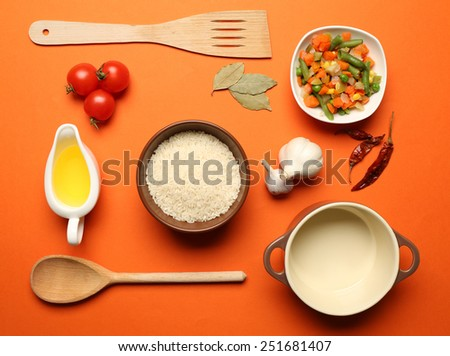Food ingredients and kitchen utensils for cooking on orange background - stock photo