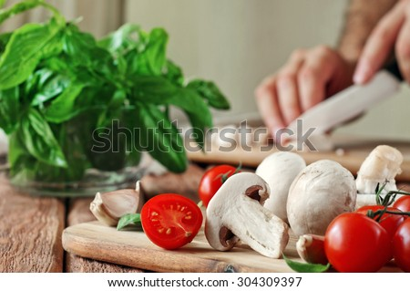 Food ingredients for pizza or pasta dishes. Fresh cherry tomatoes, mushrooms, garlic, basil leaves. Close-up. Copy space. Free space for text. In the background a men hand chopped mushrooms - stock photo