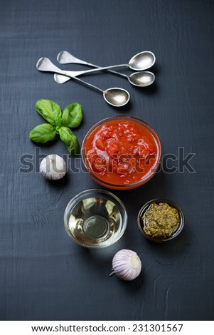 Food ingredients - pesto, chopped tomatoes, olive oil and garlic - stock photo