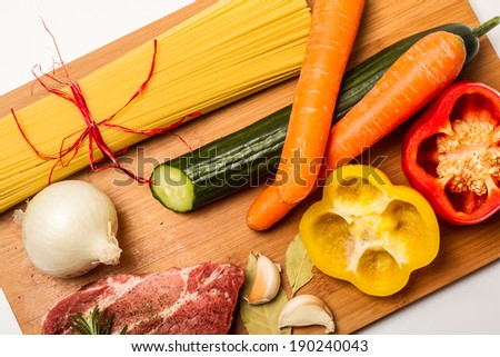 Food ingredients scattered around the chopping board background - stock photo