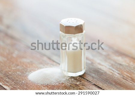 food, junk-food, cooking and unhealthy eating concept - close up of white salt cellar on wooden table - stock photo