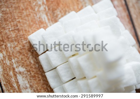 food, junk-food, cooking and unhealthy eating concept - close up of white sugar pyramid on wooden table - stock photo