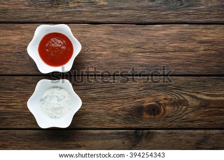 Food - ketchup and mayonnaise sauce. Two sauces at wood. Dip and dressing at wooden table. Pair of sauces top view. Flat lay. Tomato and sour cream sauces in white bowls.  - stock photo