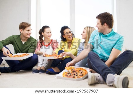 food, leisure and happiness concept - five smiling teenagers eating pizza at home - stock photo