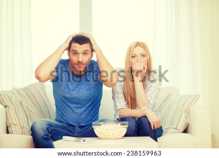 food, love, family, sports, entretainment and happiness concept - upset couple after sports team loss - stock photo