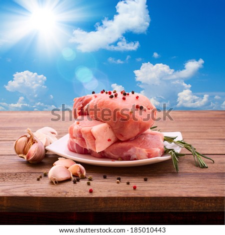 Food, meat, pork. Meat barbecue with spices on wooden surface. Meat steak. Beef steak bbq. Tomatoes, peppers, spices for cooking meat. Sky, sun, clouds background. Space for text menu diet recipe. - stock photo