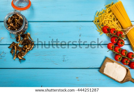Food or cooking background with pasta, tomato, spaghetti, penne, mushroom and flour on blue wood table.Top view.Copy space. - stock photo