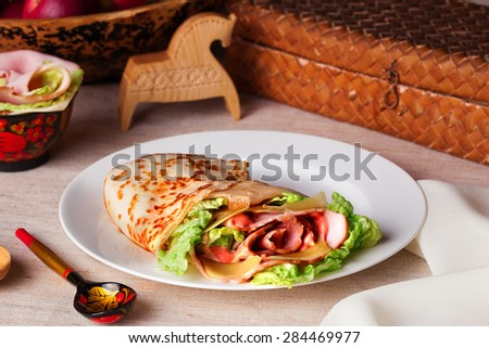 food pancake ham cheese lettuce and sauce on a plate in a still life rustic - stock photo