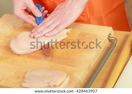 Food preparing, cooking concept. Male hands chef cutting raw chicken meat breast on wooden board close up - stock photo