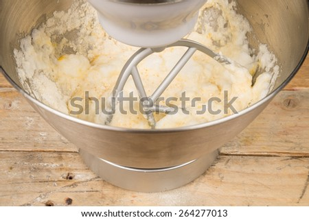 Food processor with beater tool preparing dough for a cake - stock photo