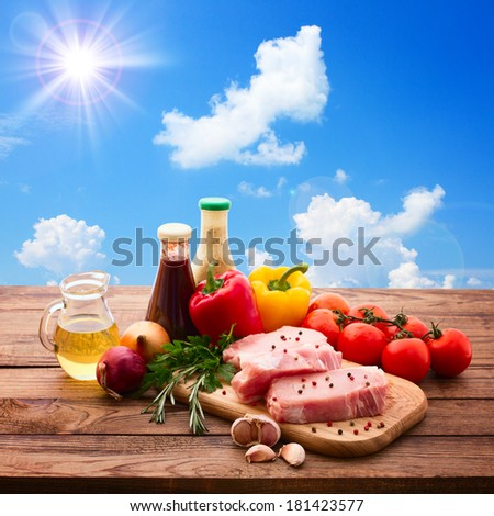 Food, raw meat for barbecue with fresh vegetables on wooden surface. Raw meat steak, steak barbecue, tomatoes, peppers, spices for cooking meat. Collage, sun, sky, clouds. Free space for text. - stock photo