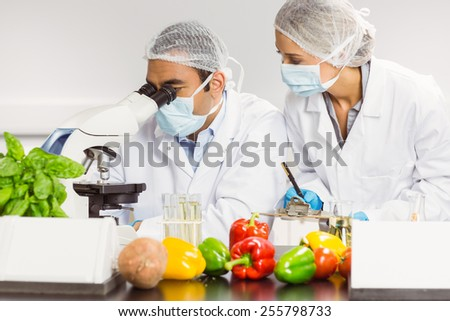 Food scientists using the microscope for research at the university - stock photo
