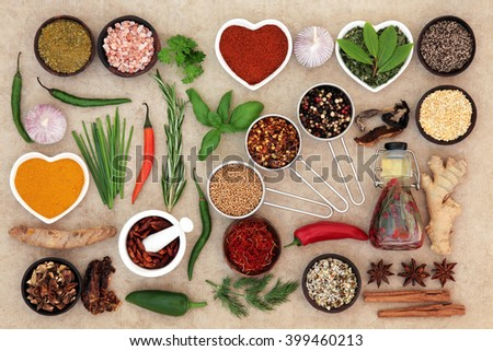 Food seasoning with herb and spice selection and chili olive oil over natural hemp paper background. - stock photo