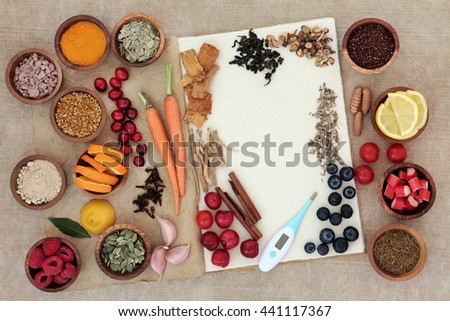Food selection for cold and flu cure to boost immune system with thermometer, high in vitamins, anthocyanins, antioxidants and minerals in wooden bowls over white background. - stock photo