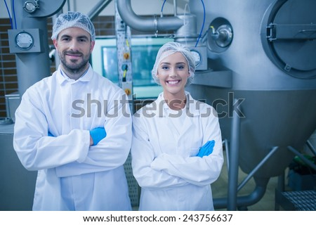 Food technicians smiling at camera in a food processing plant - stock photo