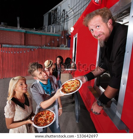 Food truck owner serving pizza to happy couple - stock photo
