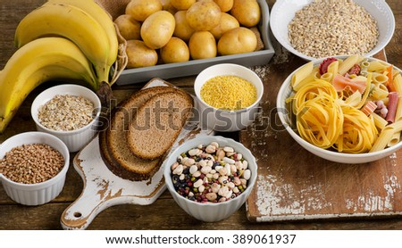 Foods high in carbohydrate on a rustic wooden table. Top view - stock photo