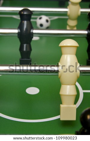Foosball and soccer game table with ball in background - stock photo