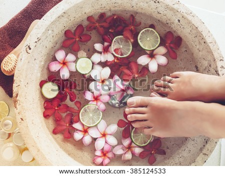 Foot bath in bowl with lime and tropical flowers, spa pedicure treatment, top view - stock photo