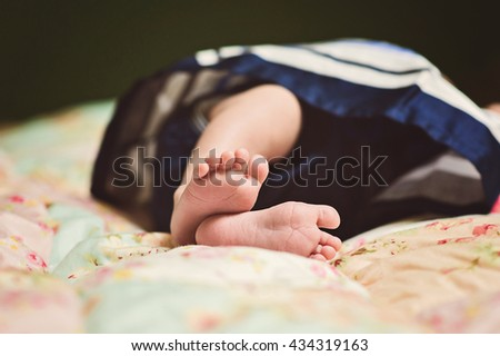 Foot legs of newborn baby in a little blue  skirt. - stock photo