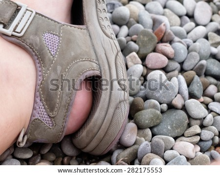 foot male in sandals on a background sea pebbles         - stock photo
