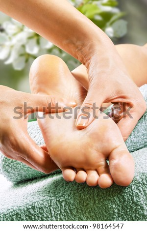 Foot massage in the spa salon in the garden - stock photo
